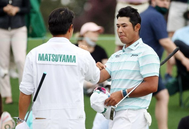 Hideki Matsuyama with his caddie after finishing on the 18th green in the third round of the Masters at Augusta National Golf Club. Picture: Kevin C. Cox/Getty Images.