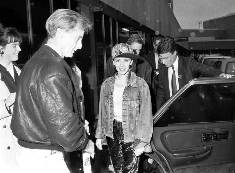 Australian pop singer Kylie Minogue smiles for the photographer before getting into her car in Edinburgh Airport in October 1989.