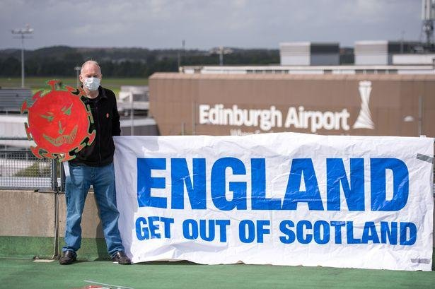 An activist stages protest at Edinburgh Airport, demanding English tourists do not travel to Scotland.