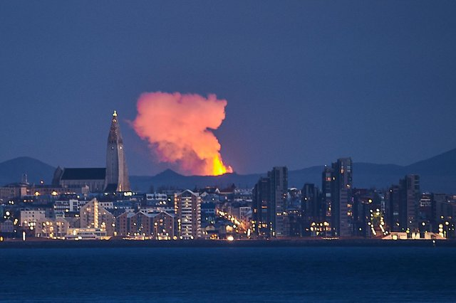 Icelandic capital Reykjavik is seen with the glow from the lava coming out of a volcanic fissure on the Reykjanes Peninsula behind in May this year (Picture: Halldor Kolbeins/AFP via Getty Images)
