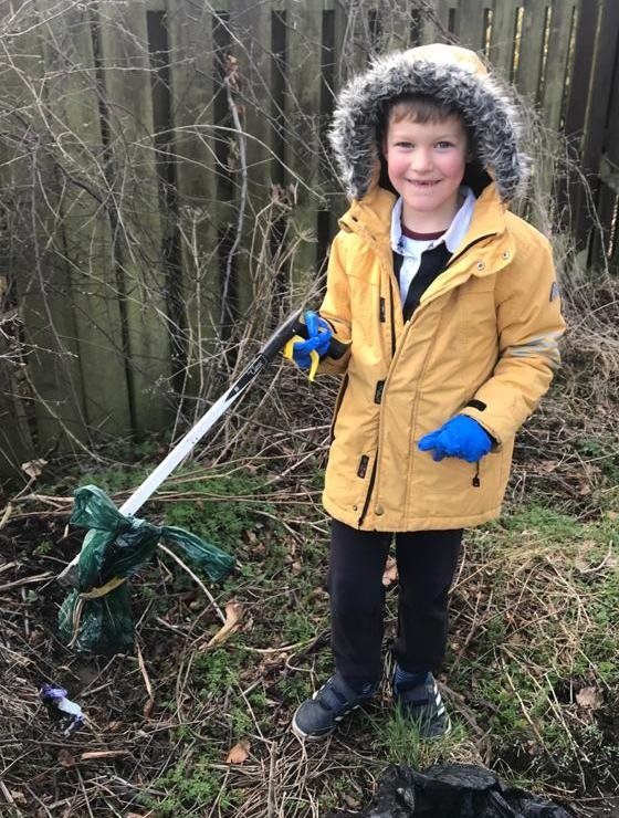 Archie Barry, seven, helping clear up the farm in Ratho.