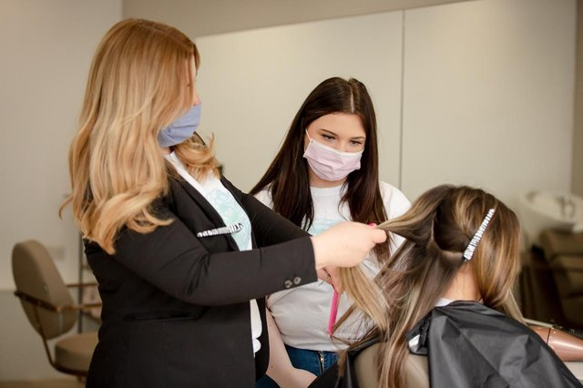 Salon owner Kerry Anderson teaching new pupil.