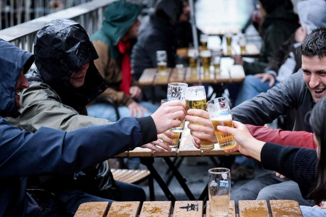 Friends toast each other as they drink a beer on a terrace in Brussels, on May 8, 2021, as the Belgium government eased the restrictions put in place to curb the spread of the coronavirus Covid-19. (Photo by Kenzo TRIBOUILLARD / AFP) (Photo by KENZO TRIBOUILLARD/AFP via Getty Images)