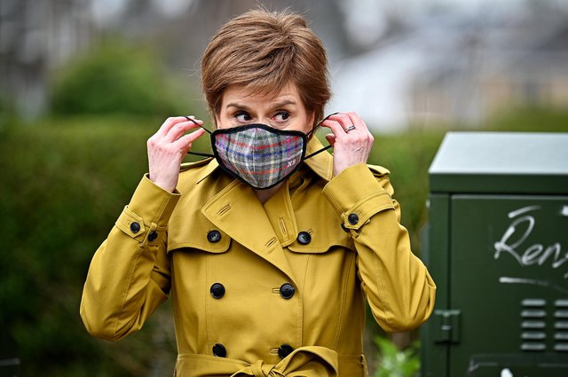 First Minister and leader of the SNP Nicola Sturgeon puts on a mask following a visit to Burnside chemist during campaigning in Rutherglen. Picture: Jeff J Mitchell/Getty Images