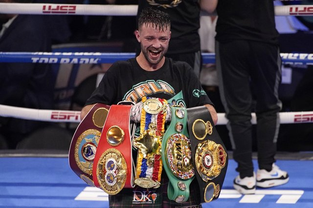 Josh Taylor celebrates while holding his belts after defeating Jose Ramirez by unanimous decision