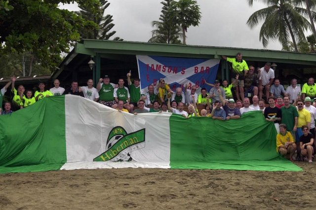 Hibs fans assemble for a picture, with a Tamson's Bar flag visible in the background