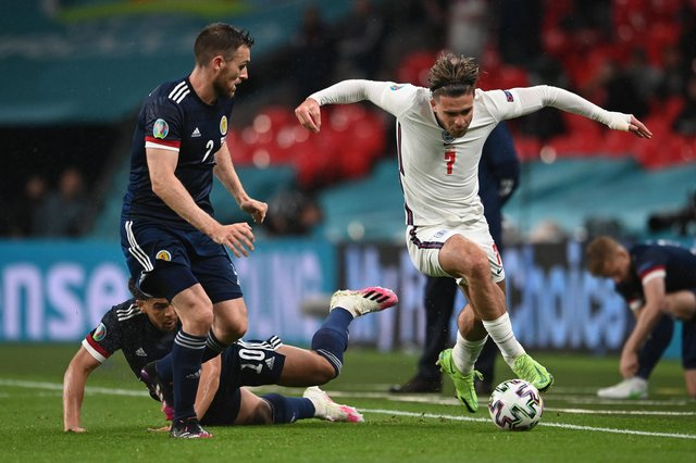 Jack Grealish runs with the ball whilst under pressure from Stephen O'Donnell and Che Adams
