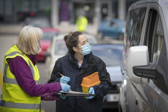A nurse and volunteer talk to patients in their vehicle at one of the new the drive-thru flu clinics at Little France, Edinburgh.
