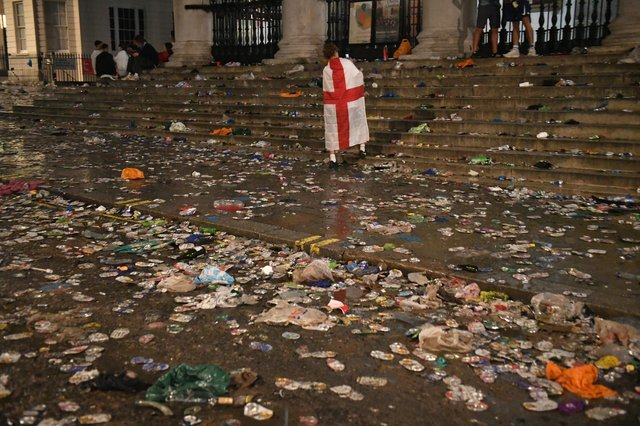A lone fan walks amongst litter strewn on the ground in front of St Martin-In-The-Fields church in Trafalgar Square, London, after Italy beat England on penalties to win the Euro 2020 final (Picture: Dominic Lipinski/PA)