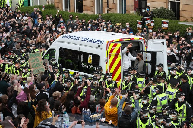 Lakhvir Singh and Sumit Sehdev are released from the back of a Home Office immigration enforcement van in a Glasgow street after crowds of people prevented it from leaving (Picture: Andrew Milligan/PA)