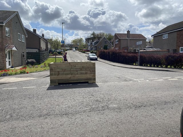 Planter installed at the junction of Barberton Mains Wynd, Edinburgh, as part of a new council scheme, 'Spaces for People'.See SWNS story SWSCplanter. A planter has been installed in the middle of a busy road junction - leaving residents flabbergasted.  The wooden box filled with soil was installed at the junction of Barberton Mains Wynd, Edinburgh, as part of a new council scheme, 'Spaces for People'. Residents fear emergency services could be unable to enter the road, and that the wooden box could block visibility for drivers and lead to a child being knocked down as they left nearby Juniper Green Primary School. The idea of the planter is to keep children travelling to the primary school safe by restricting access at the junction to residents of the street, blue badge holders, school staff, deliveries, waste collection, and emergency services.