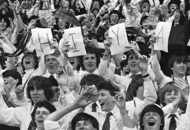 """Youngster hold up a HIYA sign for Pope John Paul II at Murrayfield during the Papal visit to Scotland in May 1982. 40.000 young people from all over Scotland came for the Scottish National Youth Pilgrimage, singing 'You'll Never Walk Alone"""" and chanting John Paul, John Paul."""